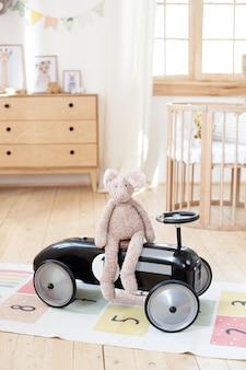 Pluszowy królik siedzi w wyścigowym samochodzie dla dzieci w pokoju dziecięcym. wnętrze w stylu skandynawskim. samochód dziecięcy w stylu retro w dziecięcej sypialni. zabawki dla dziecka w przedszkolu. rustykalny. hygge