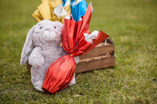 Pluszowy królik trzymający na trawie brazylijskie jajo eastersa