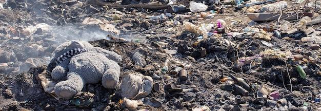 Pluszowy miś leży wyrzucony pośrodku dymiącego wysypiska śmieci