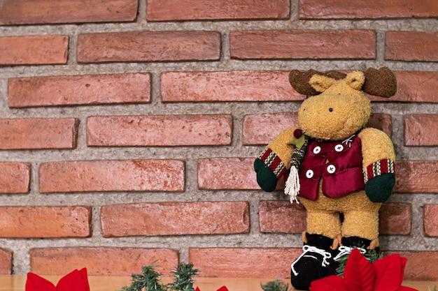 Pluszowy renifer w szaliku i rękawiczkach, stojący na dwóch nogach, przed ceglanym tłem na drewnie
