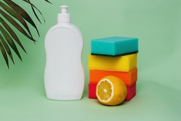 Płyn do mycia naczyń z gąbkami i cytryną na zielonym tle