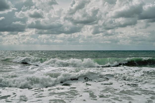 Płynące fale na plaży, słoneczny i wietrzny letni dzień z pochmurnym niebem, idealna pogoda do surfowania. widok morza