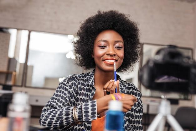 Płynna warga. niesamowita kobieta z kręconymi włosami wyglądająca na zadowoloną podczas przymierzania nowej wargi w płynie.