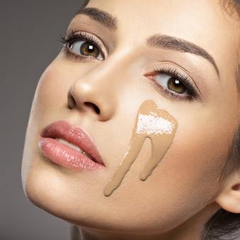 Płynny podkład kosmetyczny do makijażu nakładany jest na kobiecą twarz. koncepcja zabiegów kosmetycznych. dziewczyna robi makijaż.