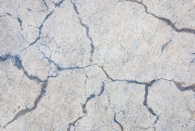 Płyta betonowa z przypadkowymi pęknięciami, szary beżowy kamień tekstura tło