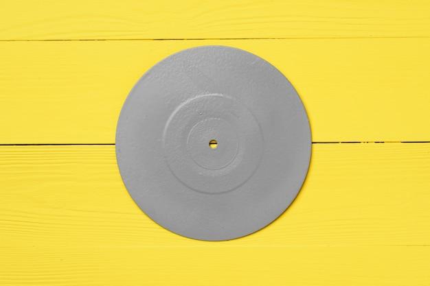 Płyta cd pomalowana na szaro na żółtym tle