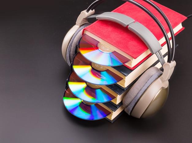 Płyta cd wystaje ze stosu czerwonych książek ze słuchawkami na książkach