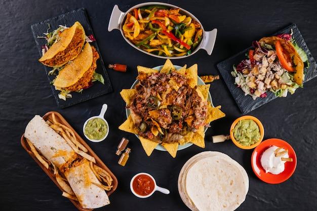 Płyta z nachos pośród meksykańskiego jedzenia