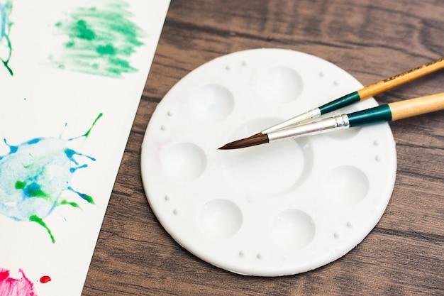 Płyta z płytkami o mieszanym kolorze wody palety farb i pędzle do kolorowania służą do rysowania akwareli na papierze. aby tworzyć sztukę