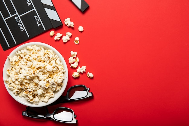 Płyta z popcornem i kino klakier na czerwonym tle. miejsce na tekst
