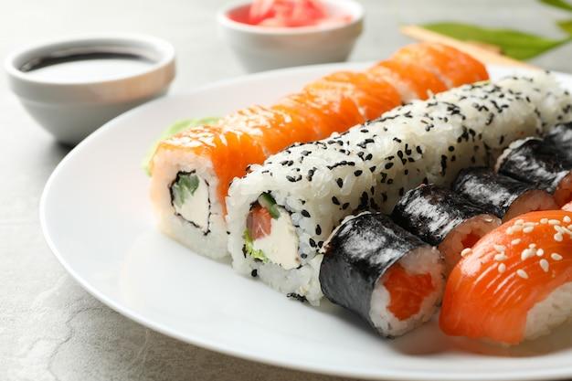Płyta z rolki sushi na szarej powierzchni. japońskie jedzenie