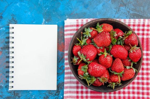 Płyta z widokiem z góry z truskawkami, świeżymi, smacznymi owocami na niebieskim tle