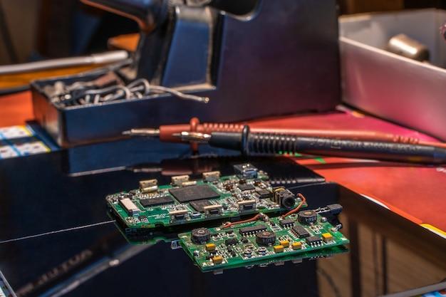 Płytka drukowana z innymi urządzeniami na czarnym stole inżynier w miejscu pracy stock photo