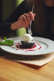 Płytka głębokość spienionego zdjęcia ciasta brownie z lodami. ręka dziewczyny z widelcem.