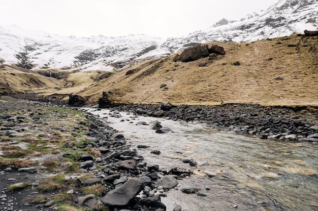 Płytka mała górska rzeka płynie kaskadą z pokrytych śniegiem gór do wąwozu