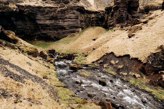 Płytka szybka górska rzeka w niebezpiecznym wąwozie między górami w islandii