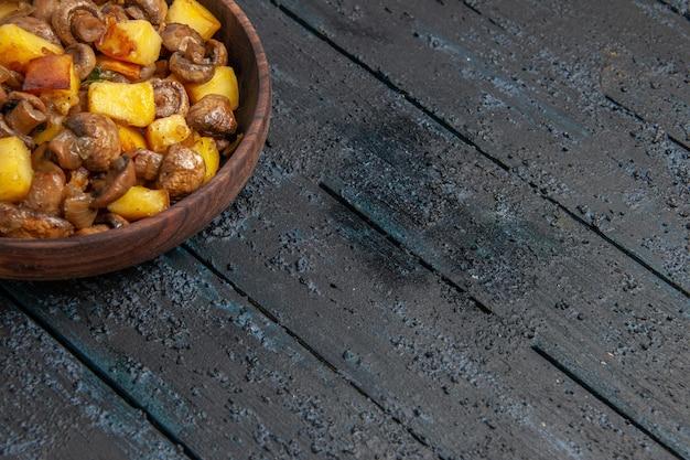 Płytka z widokiem z góry z brązową miską z ziemniakami i grzybami w lewym górnym rogu stołu
