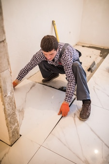 Płytkarz pracownik budowlany układa płytki, klej do płytek ceramicznych. układanie płytek ceramicznych.