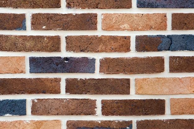 Płytki elewacji domu, czarne tło ściany z cegły.