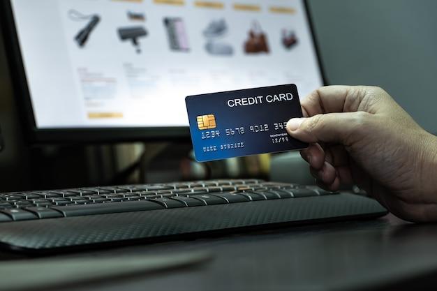 Płytkie focus ręka trzymać karty kredytowej na klawiaturze komputera