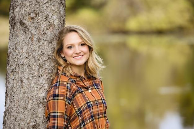 Płytkie fokus strzał pięknej kobiety opierając się o drzewo i uśmiechając się do kamery
