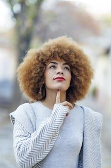 Płytkie skupienie zamyślonej latynoskiej kobiety z kręconymi włosami dotykającej podbródka w parku