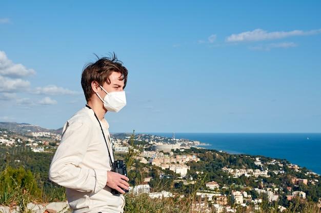 Płytkie ujęcie fokus atrakcyjnego młodego człowieka stojącego na wzgórzu, patrząc na nadmorskie miasto podczas pandemii