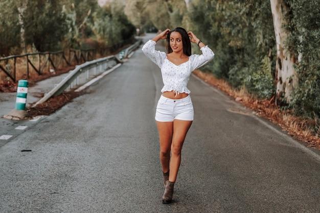 Płytkie ujęcie ładnej dziewczyny w bieli na autostradzie