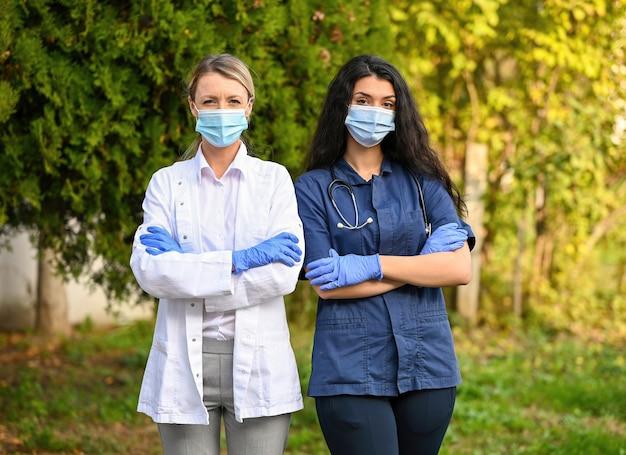 Płytkie ujęcie lekarzy noszących maski na zewnątrz na zewnątrz