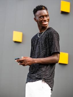 Płytkie ujęcie młodego czarnego mężczyzny na szarej ścianie