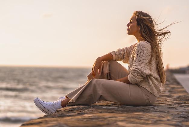 Płytkie ujęcie młodej blondynki w wełnianym sweterku