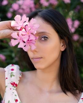 Płytkie ujęcie młodej brunetki rasy kaukaskiej z różowymi kwiatami w dłoni
