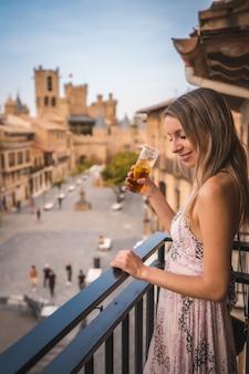 Płytkie ujęcie ostrości kobiety rasy kaukaskiej na balkonie z widokiem w niemczech