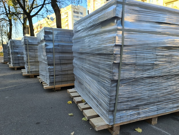 Płyty chodnikowe w folii plastikowej leżące na drewnianej palecie na ulicy