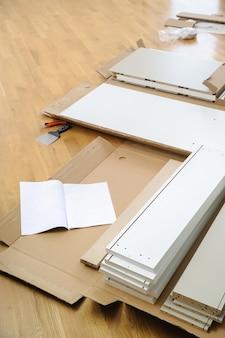 Płyty meblowe i łączniki znajdują się na podłodze pomieszczenia