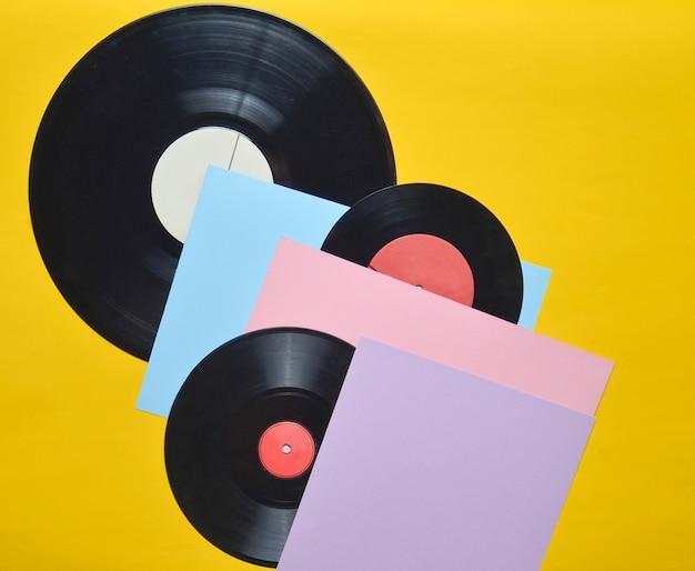 Płyty winylowe na kolorowej pastelowej powierzchni. atrybuty muzyczne retro z lat 80. widok z góry, minimalizm. skopiuj miejsce
