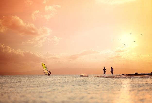 Pływać po morzu podczas zachodu słońca