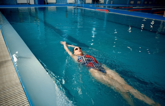Pływaczka w stroju kąpielowym, czapce i okularach pływających na plecach w basenie