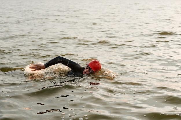 Pływaczka w stroju kąpielowym pływająca w jeziorze podczas zawodów sportowych na świeżym powietrzu