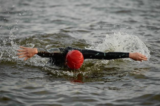 Pływaczka w stroju kąpielowym pływająca w specjalnym stylu w morzu podczas zawodów