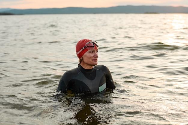 Pływaczka w stroju kąpielowym pływanie w jeziorze podczas zachodu słońca na zewnątrz