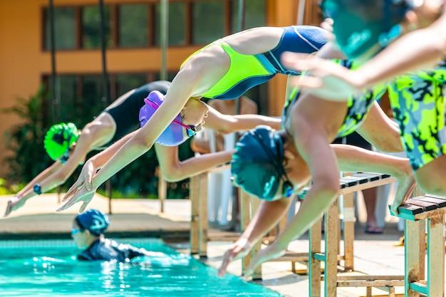 Pływaczki oung skaczą z platformy do basenu, aby popływać