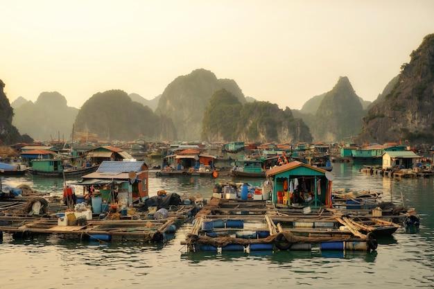 Pływająca wioska cai beo o zachodzie słońca w zatoce ha long