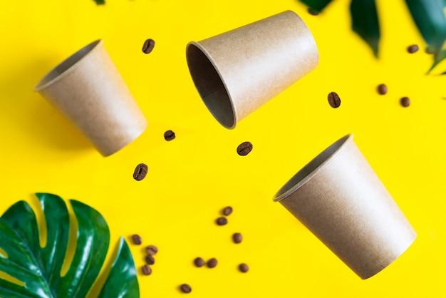 Pływające, ekologiczne papierowe jednorazowe kubki na makietach nad żółtym tłem z zielonymi liśćmi palmowymi. zero marnowania