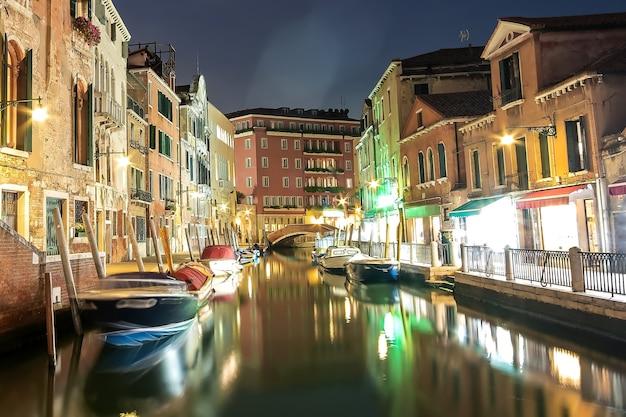 Pływające łodzie i odbicia światła w kanałach woda w wenecji, włochy.