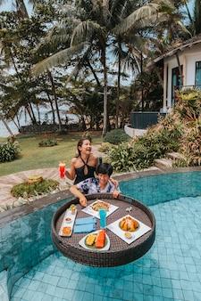 Pływające śniadanie w basenie bez krawędzi na rajskim basenie, rano w tropikalnym bungalowie