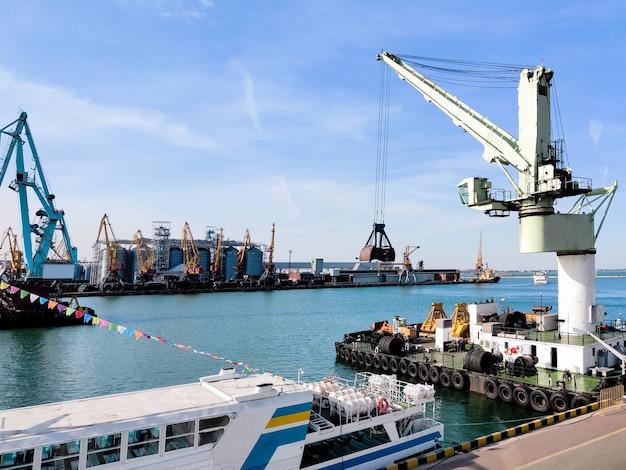 Pływający dźwig towarowy z kadzią w porcie morskim nad morzem oraz windy spichlerz, pomoc holownicza, łodzie i dźwigi. przemysłowa sceneria morskiego portu towarowego