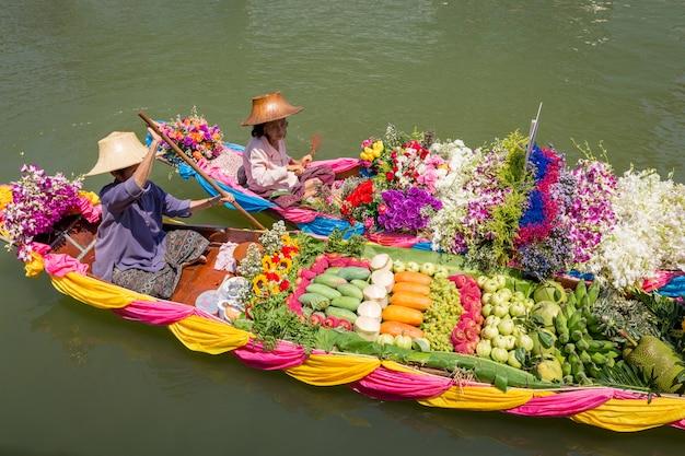Pływający targ z owocami, warzywami i różnymi przedmiotami sprzedawanymi z małych łodzi