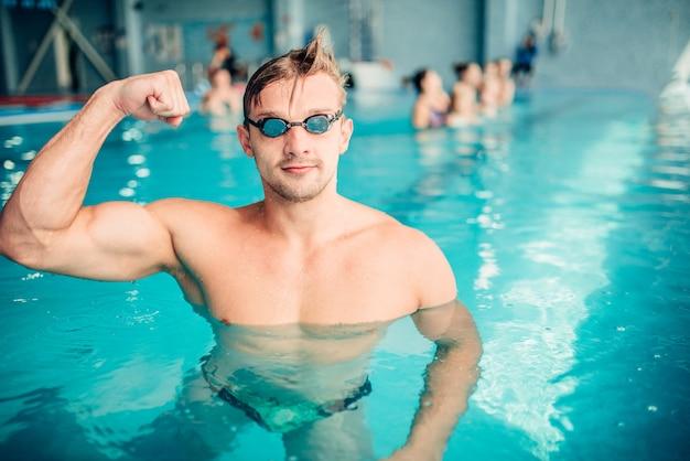 Pływak atletyczny pokazuje mięśnie, sporty wodne