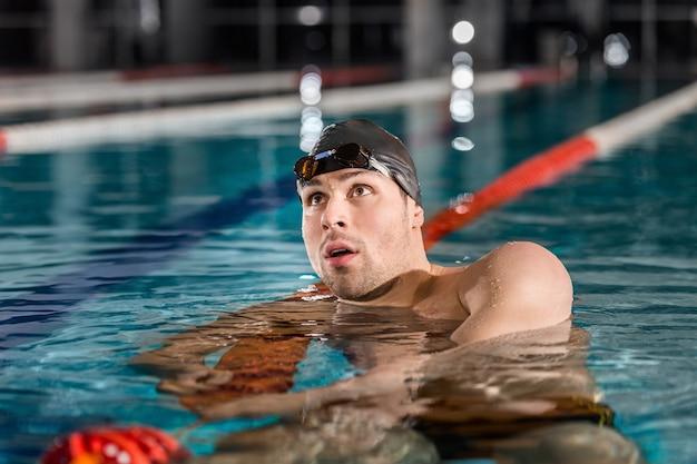 Pływak odpoczywa na linii pływa po wyścigu pływackim
